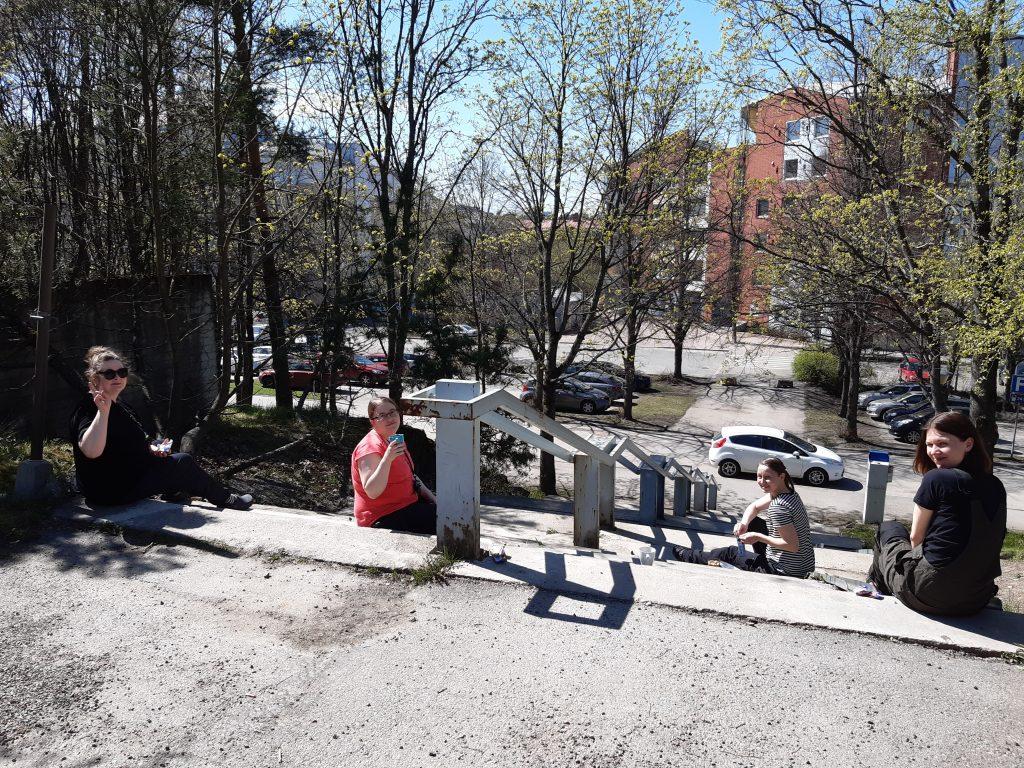Neljä Yliopistomuseon työntekijää istuu rappusilla auringonpaisteesssa.