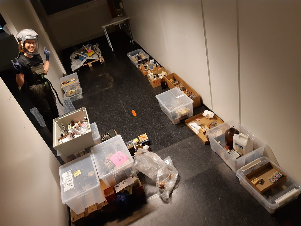 Ruskeasuon muista kokoelmista erotellut kemikaalipakkaukset on asteltu lattialle pahvi- ja muovilaatikoihin. Yliopistomuseon työntekijä seisoo huoneen oviaukossa suojavarusteissa.