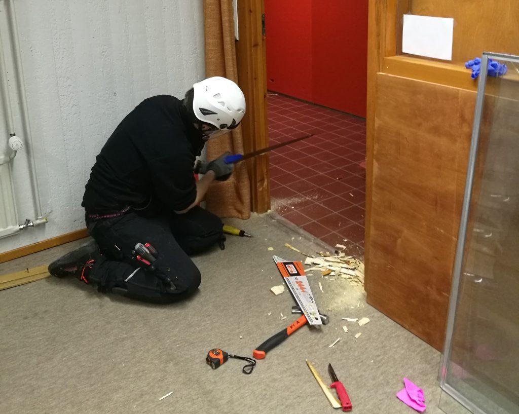 Museomestari Johannes Keltto sahaa kapean oviaukon alaosan karmeja, jotta kuormalava mahtuu ovesta ulos.